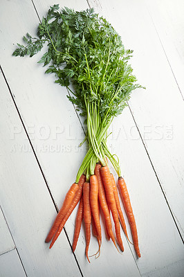 Buy stock photo Shot of a bunch of fresh carrots on a table