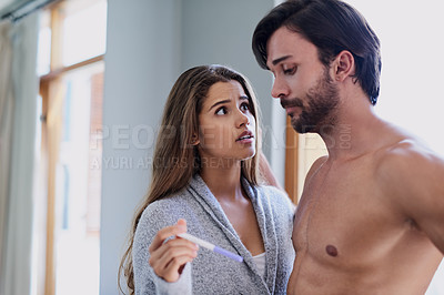 Buy stock photo Shot of a young couple looking worried while taking a pregnancy test at home