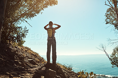Buy stock photo Rear view shot of a young woman admiring the view from the top of a mountain