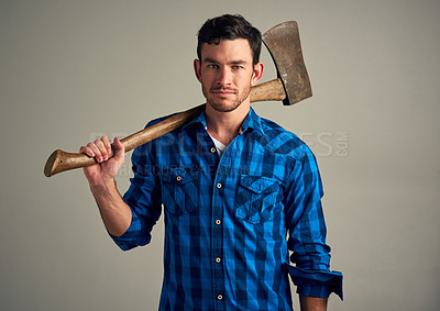 Buy stock photo Studio shot of a young male lumberjack holding an axe against a grey background