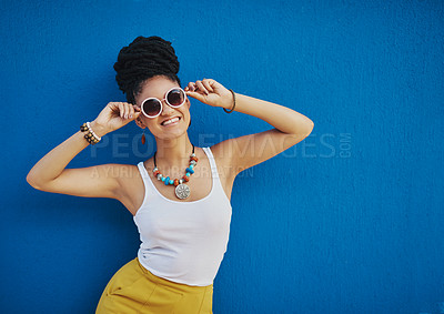 Buy stock photo Shot of an attractive young woman wearing funky sunglasses against a blue background