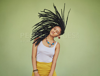 Buy stock photo Shot of an attractive young woman tossing her hair against a green background