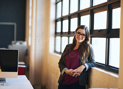 Buy stock photo Cropped portrait of an attractive young businessman leaning against a wall in her office