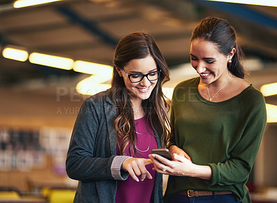 Buy stock photo Cropped shot of two young female coworkers looking at something on a cellphone