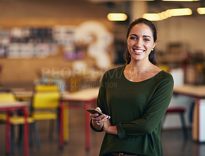 Buy stock photo Cropped portrait of an attractive young businesswoman sending a text message while standing in her office