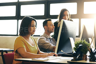 Buy stock photo Cropped shot of three young colleagues working at their desk in the office