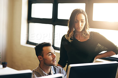 Buy stock photo High angle shot of a young businesswoman helping a male colleague in their office