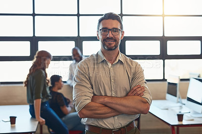 Buy stock photo Shot of a designer standing in an office with his colleagues in the background