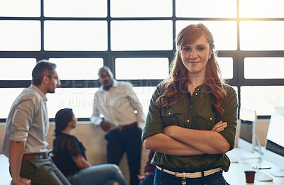 Buy stock photo Shot of a designer standing in an office with her colleagues in the background
