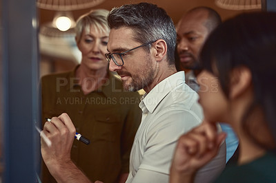 Buy stock photo Shot of a group of designers brainstorming with notes on a glass wall in an office