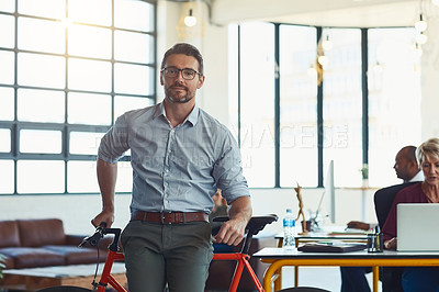 Buy stock photo Portrait of a mature designer standing in an office with his bicycle