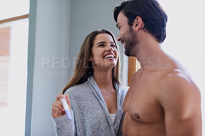 Buy stock photo Shot of a happy young couple taking a pregnancy test at home