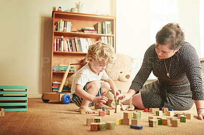 Buy stock photo Shot of a mother and her little son playing with wooden blocks at home