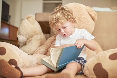 Buy stock photo Shot of an adorable little boy reading with his teddy bear at home