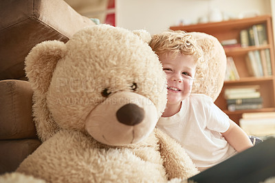 Buy stock photo Portrait of an adorable little boy sitting alongside his teddy bear at home