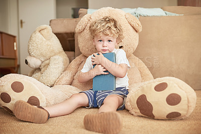 Buy stock photo Portrait of an adorable little boy reading with his teddy bear at home