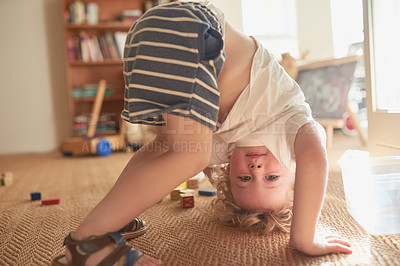 Buy stock photo Shot of an adorable little boy trying to do a handstand at home