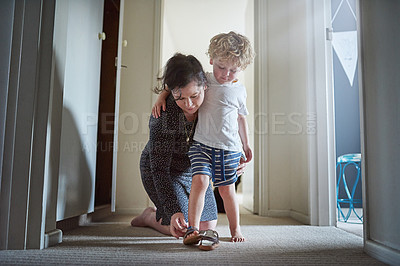 Buy stock photo Shot of a mother helping her son put his shoes on at home