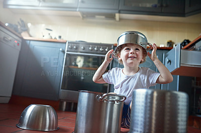 Buy stock photo Portrait of an adorable little boy playing with pots in the kitchen