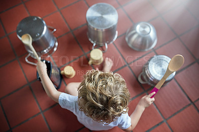 Buy stock photo High angle shot of an adorable little boy playing drums on a set of pots in the kitchen