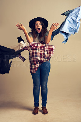 Buy stock photo Studio shot of a young woman tossing clothing against a brown background