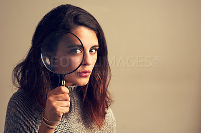 Buy stock photo Studio portrait of a young woman looking through a magnifying glass against a brown background