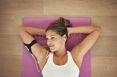 Buy stock photo High angle shot of a young woman listening to music while lying on her yoga mat
