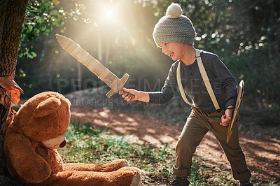 Buy stock photo Shot of an adorable little boy playing with a cardboard sword and shield outside