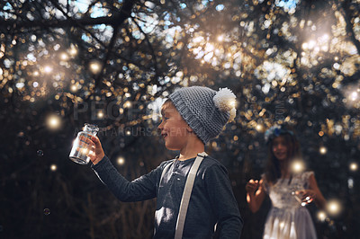 Buy stock photo Shot of two little siblings catching fireflies in jars outside