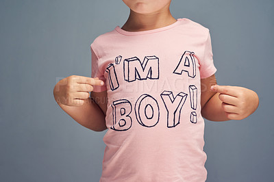 """Buy stock photo Studio shot of a boy wearing a t shirt with """"I'm a boy"""" printed on it against a gray background"""