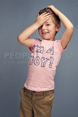 "Buy stock photo Studio portrait of a boy wearing a t shirt with ""I'm a boy"" printed on it against a gray background"