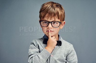 Buy stock photo Studio shot of a smartly dressed little boy looking thoughtful against a gray background