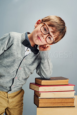 Buy stock photo Studio portrait of a smart little boy leaning over a pile of books against a gray background