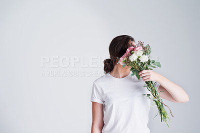 Buy stock photo Studio shot of an unrecognizable woman covering her face with flowers against a grey background