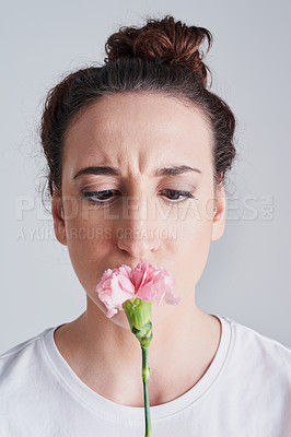 Buy stock photo Studio shot of a beautiful young woman smelling a pink flower against a grey background