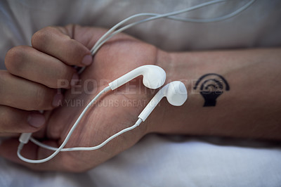 Buy stock photo Cropped shot of earphones in an unrecognizable person's closed hands and a tattoo of a speaker on his wrist