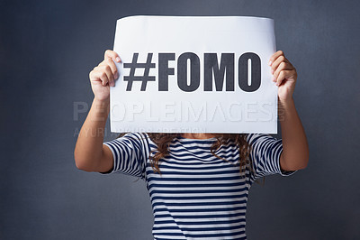 Buy stock photo Studio shot of a young woman holding a sign with #FOMO printed on it against a gray background
