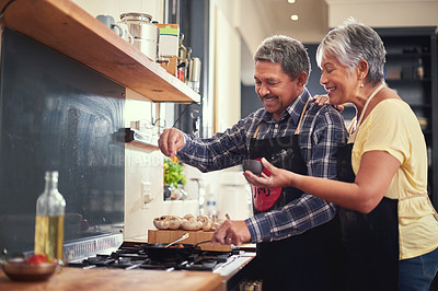 Buy stock photo Shot of a happy mature couple adding salt to a dish while cooking together at home