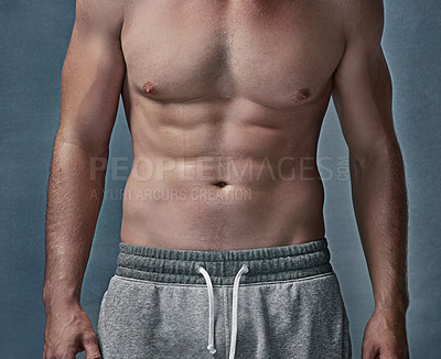 Buy stock photo Cropped shot of an unidentifiable young man's muscular abdomen in studio
