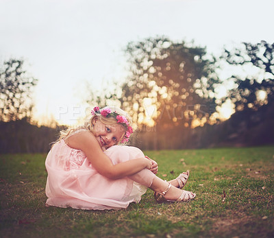 Buy stock photo Shot of a happy little girl sitting on the ground and looking at the camera outside in nature
