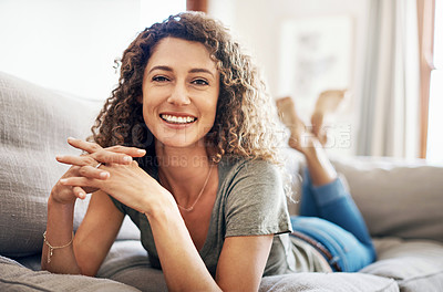 Buy stock photo Portrait of a happy young woman relaxing while lying on her couch at home