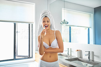 Buy stock photo Shot of a young woman brushing her teeth in the bathroom