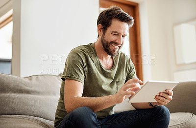 Buy stock photo Shot of a happy young man using a digital tablet on the sofa at home