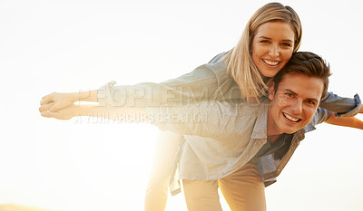 Buy stock photo Cropped portrait of a handsome young man piggybacking his girlfriend while enjoying a hike