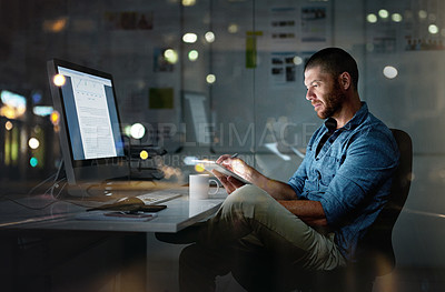 Buy stock photo Shot of a businessman using a computer and digital tablet during a late night at the office
