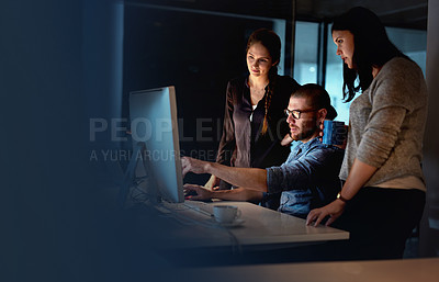 Buy stock photo Shot of a group of colleagues using a computer together during a late night at work