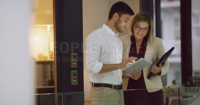 Buy stock photo Cropped shot of two businesspeople looking over a tablet while standing in the office lobby