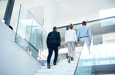 Buy stock photo Shot of a group of colleagues walking up the stairs together in a modern office