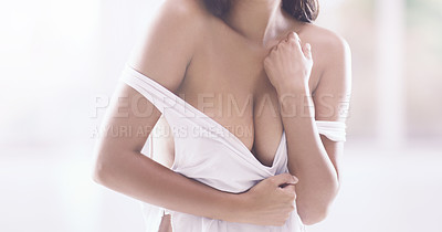 Buy stock photo Cropped shot of an unrecognizable young woman pulling on her top