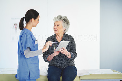 Buy stock photo Shot of a kind young nurse looking at a tablet with her elderly patient in a healthcare center